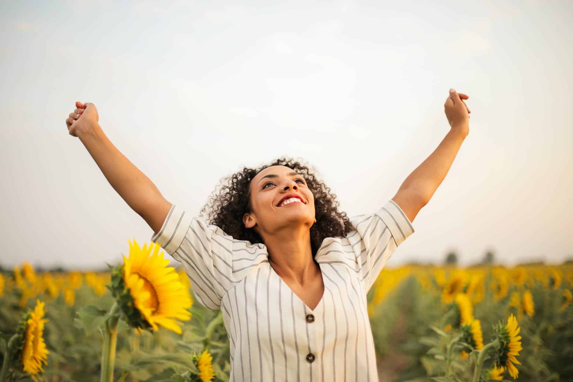 photo of woman standing on sunflower field celebrating