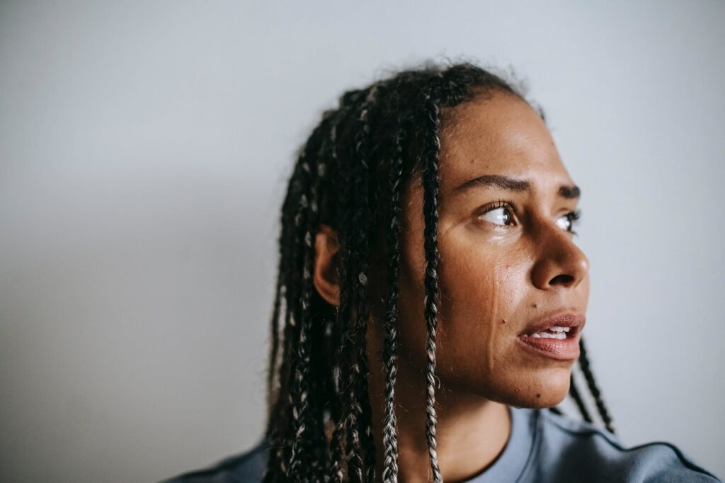 mournful black woman crying in light room
