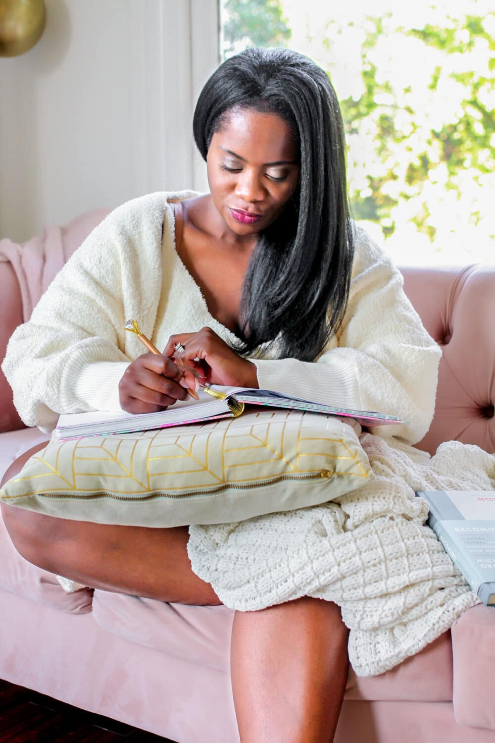woman sitting on coach writing in journal