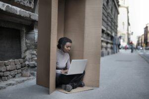 african american female sitting inside cardboard box with laptop