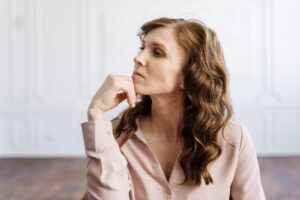 woman in white button up shirt in deep thought about mistakes