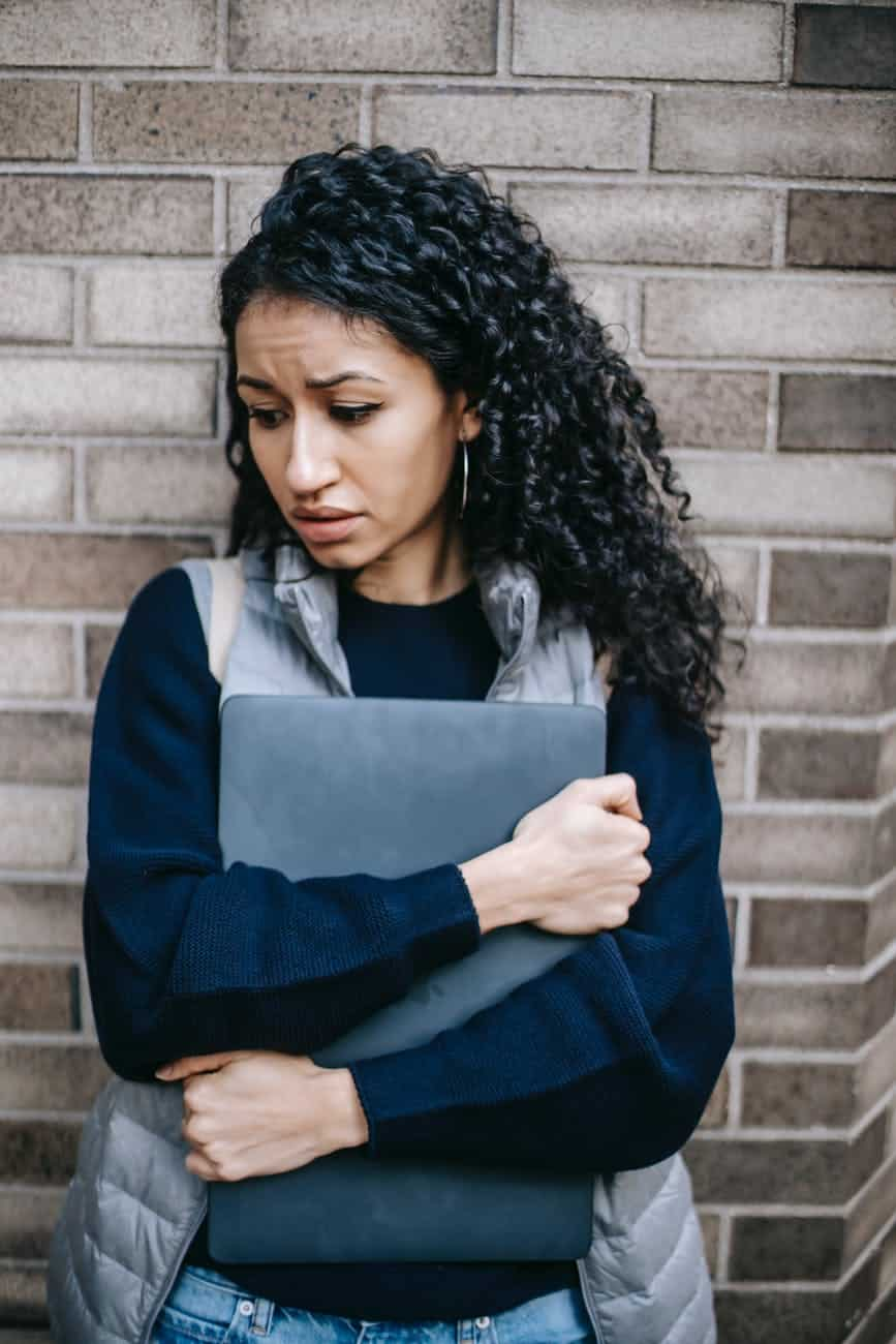 unhappy latin american woman with laptop reflecting on repeating the same mistakes