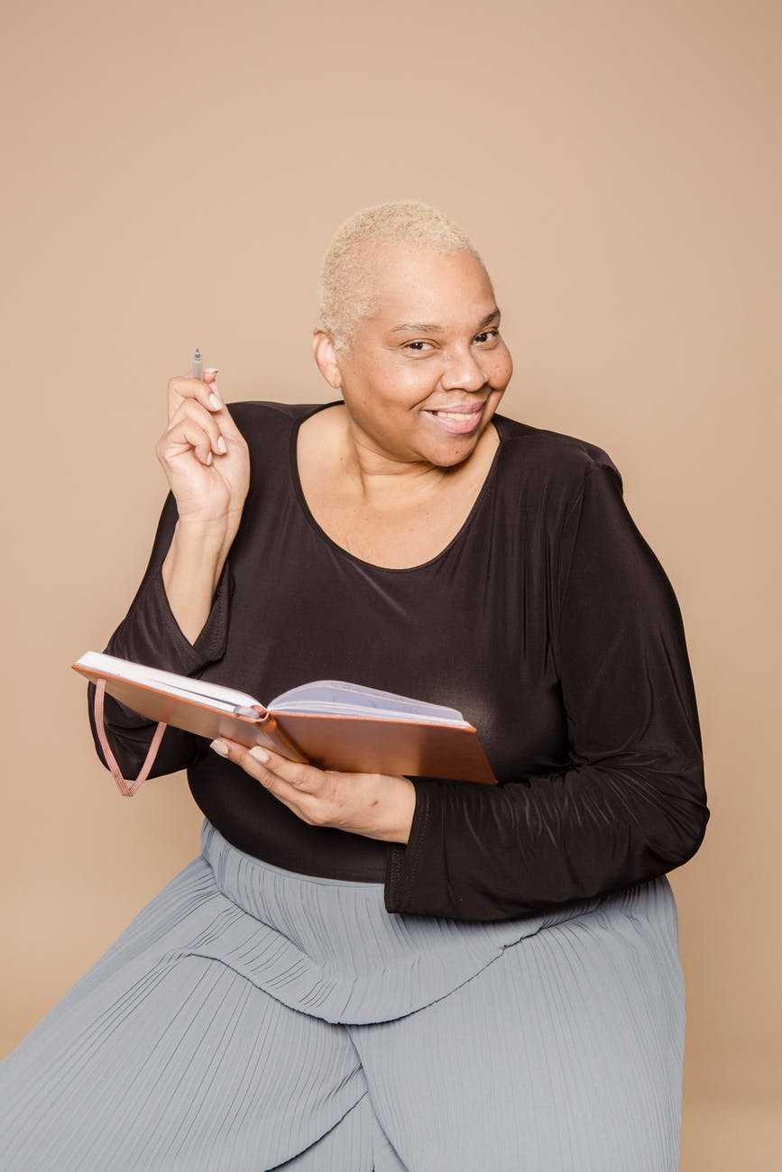 optimistic plus size black woman writing in notebook