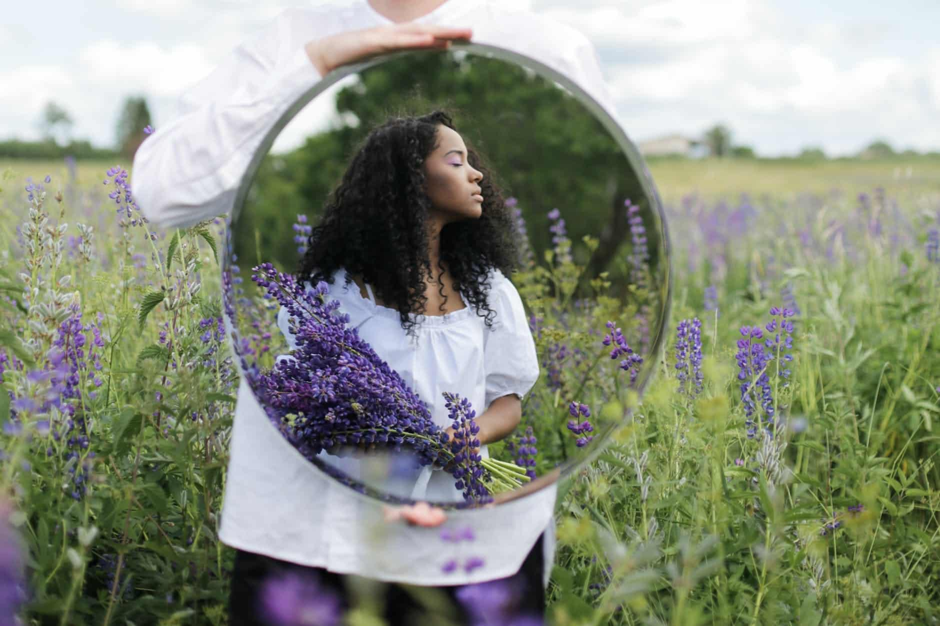 woman in white shirt holding purple flowers